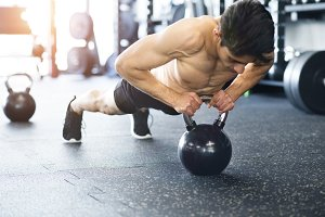 Young fit hispanic man in gym doing push ups on kettlebell.