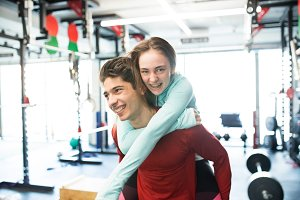 Young man in gym carrying woman on his shoulders.