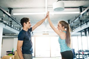 Young fit couple exercising in gym, giving high five each other.