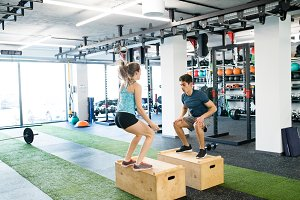 Young fit couple exercising in gym, doing box jumps.