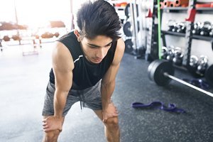 Young fit hispanic man in black sleeveless shirt in gym