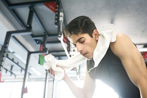 Young fit hispanic man in gym wiping sweat off his face