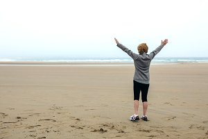 Senior woman watching the sea with hands up