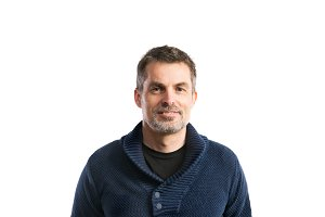 Mature hipster man in blue sweater. Studio shot, isolated.