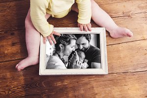 Unrecognizable baby holding family photo. Fathers day.