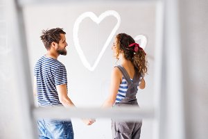 Couple painting heart on the wall in their house.