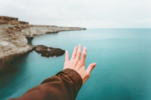Hand touching cold sea landscape