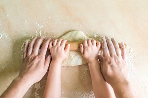 Children and dad hands rolled dough