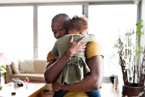 Young afro-american father with his little daughter at home.
