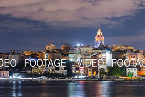 Istanbul cityscape with Galata Tower and floating tourist boats in Bosphorus night timelapse