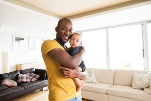 Young afro-american father holding his baby son in the arms