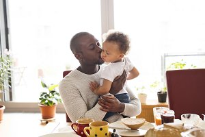 Young afro-american father with his daughter having breakfast.