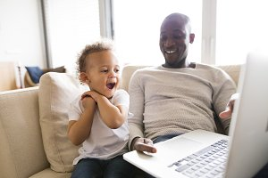 Afro-american father with little daughter at home holding laptop.