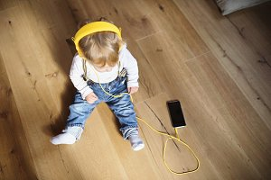 Little boy with headphones and smart phone, listening music