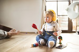 Little boy with headphones, listening music, playing musical toy