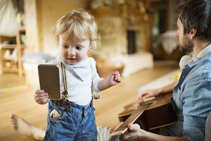 Father and son at home with smartphone and guitar.