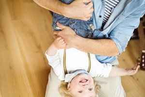 Young father at home holding his little son upside down.