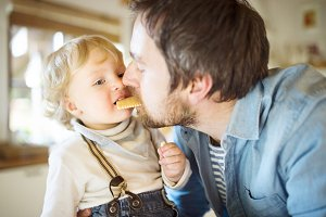 Young father at home with his little son eating biscuit together.