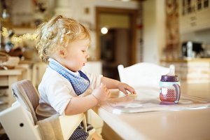Cute little boy sitting at the table, eating and drinking.
