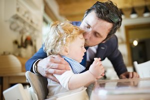 Businessman coming home, kissing little son on forehead.