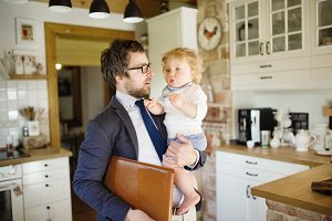 Businessman coming home, holding little son in the arms.