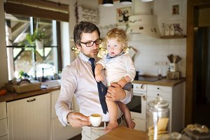 Businessman holding little son in the arms, drinking coffee.