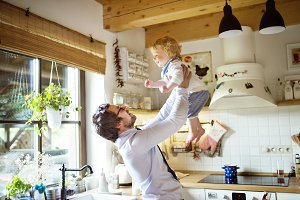 Businessman coming home, holding his son high in the air.