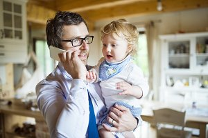 Businessman with smartphone at home with son in the arms.