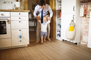 Young businessman holding hands of his son taking first steps.