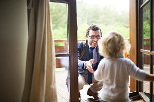 Businessman coming home, little son running into his arms.