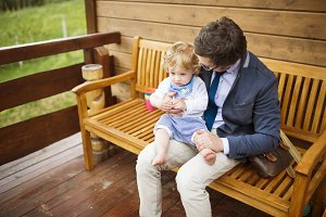 Businessman with little son sitting on front porch.
