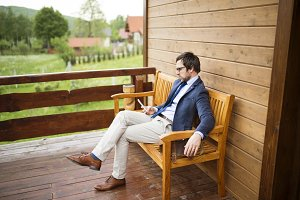 Businessman with smart phone sitting on front porch.