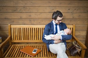 Businessman with baby daughter sitting on front porch.