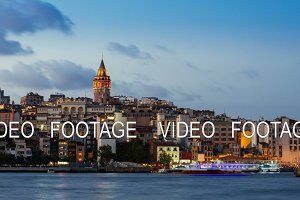 Day to night timelapse of Istanbul cityscape with Galata Tower and floating tourist boats in Bosphorus