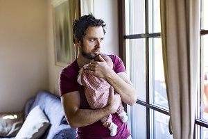 Young father at home holding his newborn baby girl.