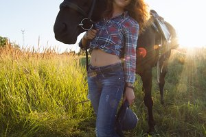 Portrait of a young woman with horse in meadow at summer day. wide angle lens