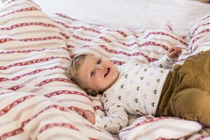 Cute little boy at home lying on bed smiling.