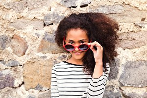 Beautiful african american girl with sunglasses against stone wa