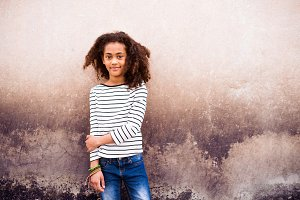 African american girl in striped t-shirt against concrete wall.