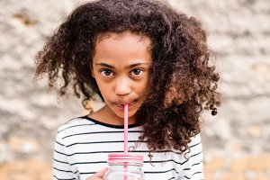 Beautiful african american girl with glass and straw, drinking.