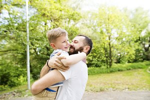 Young father with little son in green sunny nature.