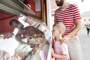 Young father and his little son buying ice cream. Sunny day.