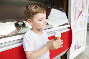 Cute little boy eating ice cream. Sunny day.