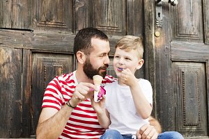 Young father and his little son eating ice cream. Sunny day.