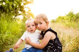 Cute little boy and girl outside in in green summer nature.