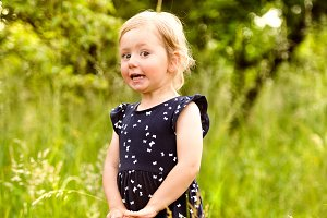 Cute little girl outside in in green sunny summer nature.