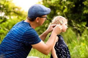Young father with daughter in nature doing her hairstyle.