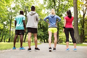 Group of young athletes prepared for run in green sunny park.