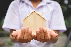 Hands boy holding little wood house