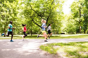 Group of young athletes running in green sunny park.